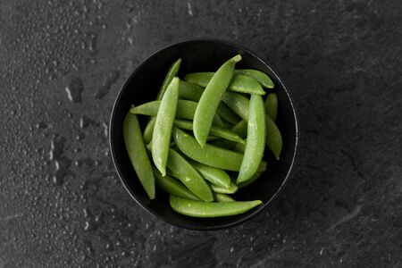 peas in bowl on wet slate stone background