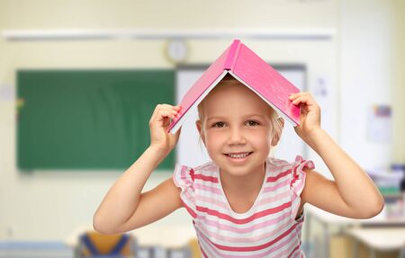 little girl of book on top of her head at school