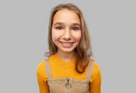 smiling teenage girl over grey background