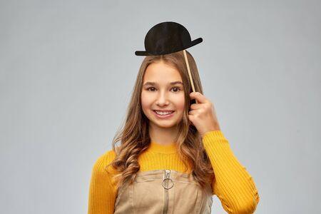 smiling teenage girl with black vintage bowler hat