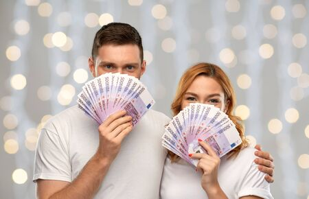 happy couple in white t-shirts with euro money