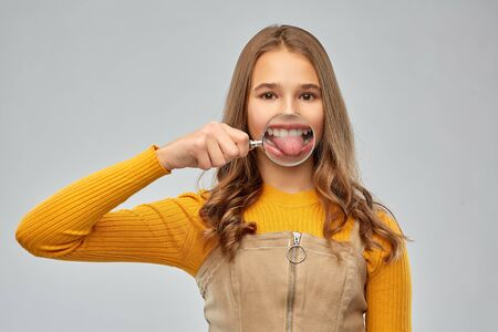 teenage girl shows tongue through magnifying glass