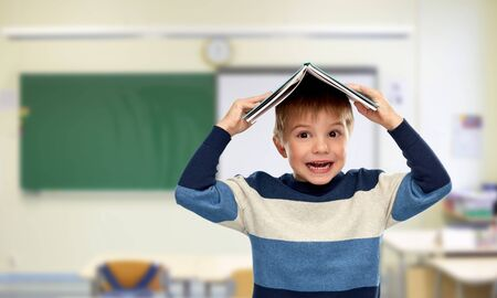 Little boy with book on top of his head at school