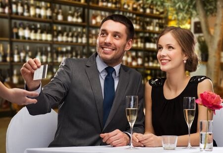 Happy couple paying with credit card at restaurant