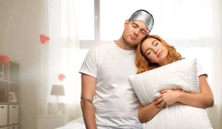 Couple with eye sleeping mask and pillow at home