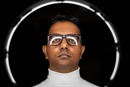Man in glasses with white illumination over black
