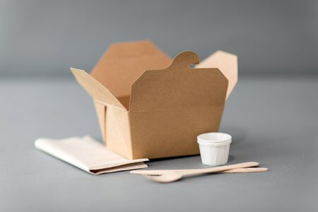 package, recycling and eating concept - disposable box for takeaway food with wooden fork, knife and napkin on table Stockfoto