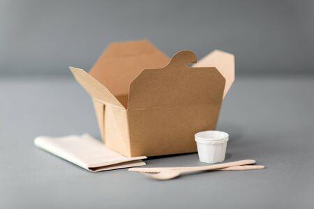 Paquete, reciclaje y concepto de alimentación: caja desechable para comida para llevar con tenedor de madera, cuchillo y servilleta en la mesa