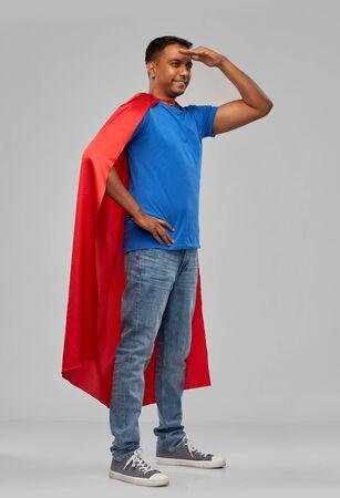 indian man in red superhero cape looking far away
