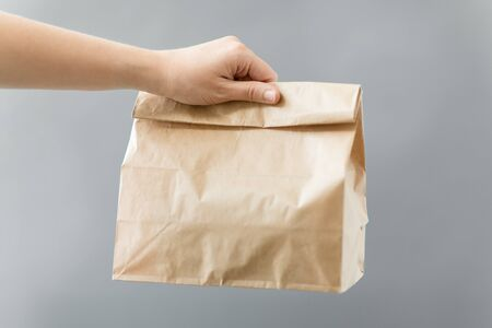 recycling and ecology concept - hand holding disposable brown takeaway food in paper bag with lunch on table