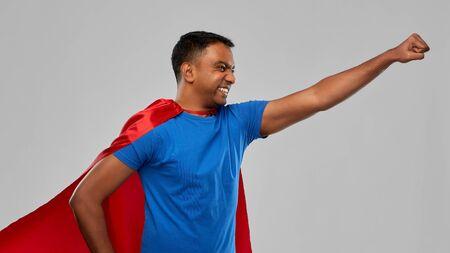 indian man in superhero cape makes winning gesture