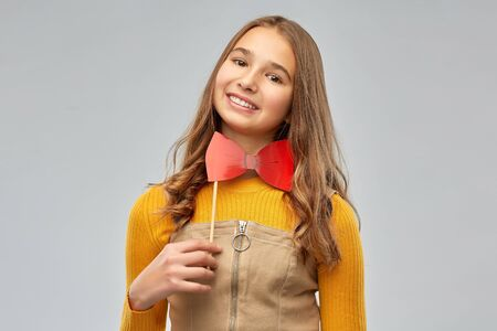 happy teenage girl with red bowtie party accessory Banque d'images - 135475538