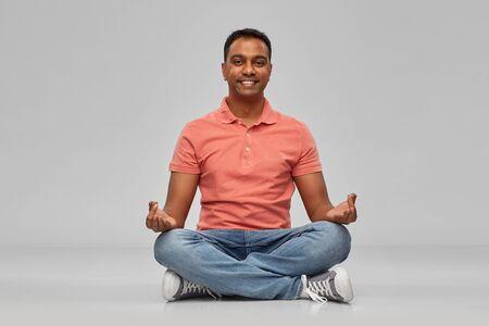 happy indian mant meditating in lotus yoga pose