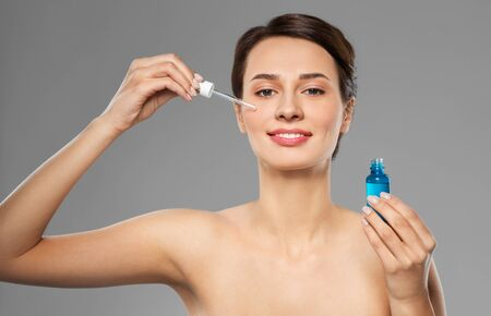 woman with dropper applying serum to her face Stock Photo