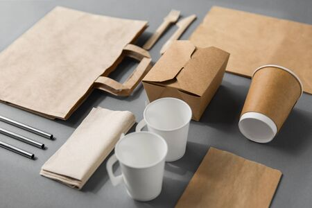 package, recycling and eating concept - disposable paper container for takeaway food with cups, bags, napkins and cutlery on table Stock Photo