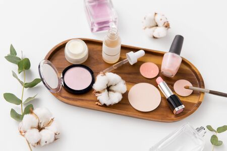beauty, natural cosmetics and make up products concept - makeup, perfume with cotton flower on wooden tray and eucalyptus cinerea