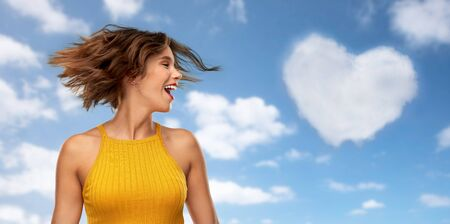 emotions and people concept - happy laughing young woman in mustard yellow top shaking head over blue sky and clouds background