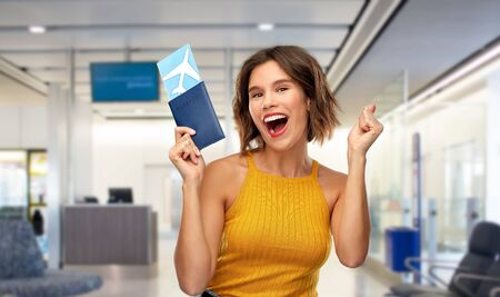 travel, tourism and vacation concept - happy laughing young woman in yellow top with air ticket and passport over airport lounge background