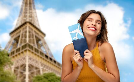 travel, tourism and vacation concept - happy smiling young woman in yellow top with air ticket and passport over eiffel tower in paris, france background