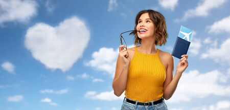 travel, tourism and vacation concept - happy young woman in mustard yellow top with air ticket and passport dreaming over blue sky and clouds background