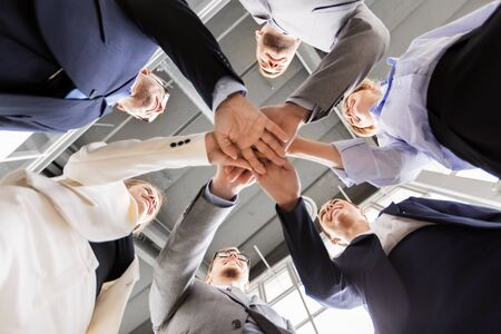 corporate, people and teamwork concept - happy business team stacking hands at office from below