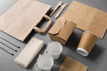 package, recycling and eating concept - disposable paper container for takeaway food with cups, bags, napkins and cutlery on table