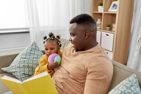 african father reading book for baby daughter