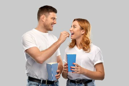 happy couple in white t-shirts eating popcorn