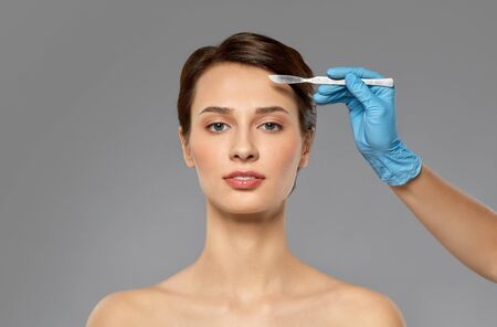 beautiful young woman and hand with scalpel