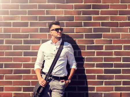 young man in sunglasses with bag over brickwall Banque d'images - 135786623
