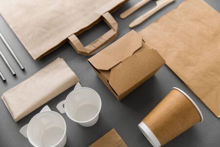 pacchetto, riciclaggio e concetto di mangiare - contenitore di carta usa e getta per cibo da asporto con tazze, sacchetti, tovaglioli e posate sul tavolo Archivio Fotografico