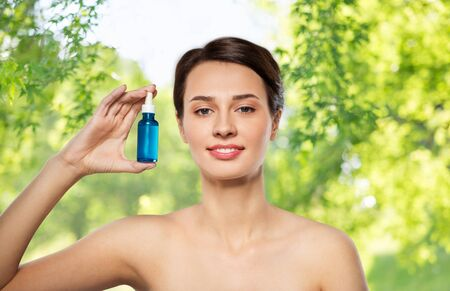 beautiful young woman with bottle of serum Stock Photo