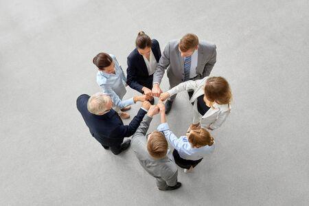 Unternehmens-, Menschen- und Teamwork-Konzept - glückliches Geschäftsteam, das Fauststoß macht