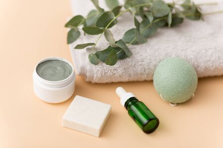 serum, clay mask, oil and eucalyptus on bath towel Stock Photo