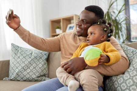 happy father with baby taking selfie at home Stock Photo
