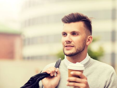 young man with bag drinking coffee in city