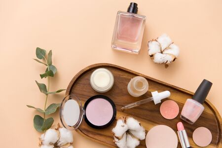 makeup, perfume and cosmetics on wooden tray