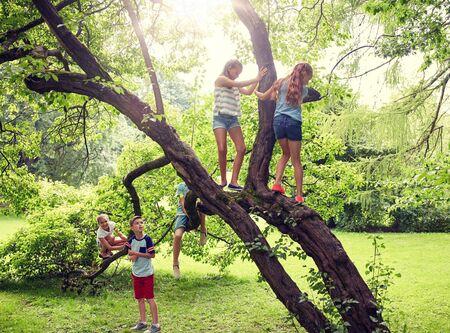 Freundschaft, Kindheit, Freizeit und Menschenkonzept - Gruppe glücklicher Kinder oder Freunde, die auf den Baum klettern und Spaß im Sommerpark haben Standard-Bild