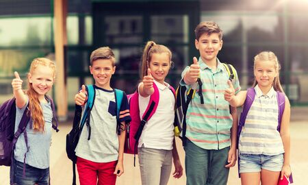 primary education, friendship, childhood, gesture and people concept - group of happy elementary school students with backpacks showing thumbs up outdoors Archivio Fotografico