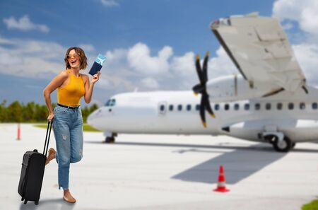 travel, tourism and vacation concept - happy laughing young woman in mustard yellow top with air ticket, passport and carry-on bag over airplane on airfield background Stock Photo