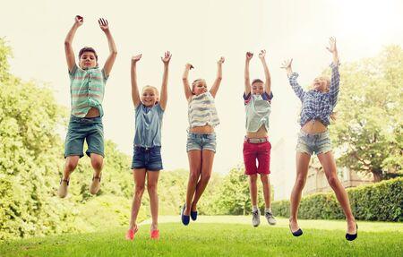 concepto de amistad, infancia, ocio y personas - grupo de niños felices o amigos saltando y divirtiéndose en el parque de verano Foto de archivo