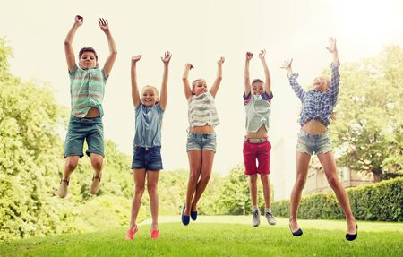 friendship, childhood, leisure and people concept - group of happy kids or friends jumping up and having fun in summer park Stock Photo