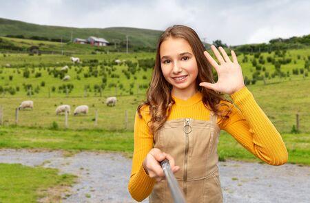 happy teenage girl taking selfie at irish country