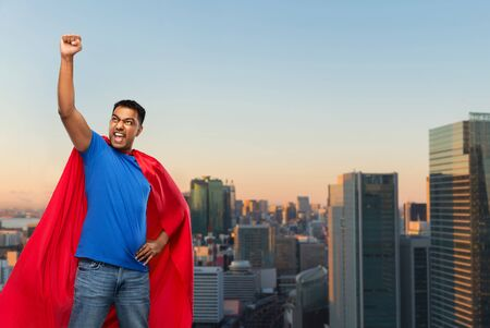 super power and people concept - indian man in red superhero cape making winning gesture over sunset in tokyo city background