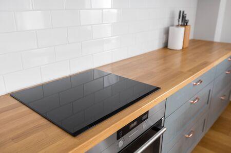 interior y concepto de cocina: encimera de cocina moderna con horno incorporado y placa eléctrica en casa