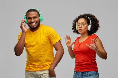 african american couple with headphones dancing