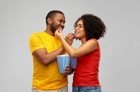 happy african american couple eating popcorn Banco de Imagens