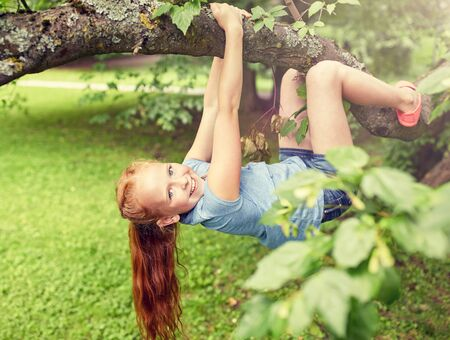 happy little girl hanging on tree in summer park Stock Photo