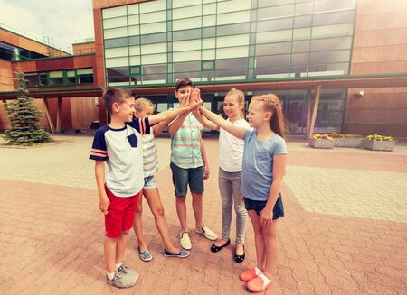 group of children making high five at school yard