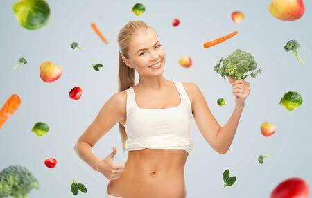 giovane donna sorridente felice con broccoli